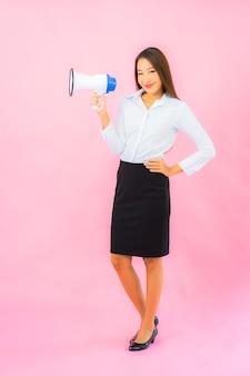 Portret pięknej młodej azjatyckiej kobiety z megafonem na różowej ścianie