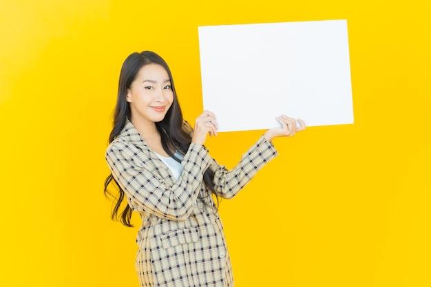 Portret pięknej młodej azjatyckiej kobiety z pustą białą tabliczką