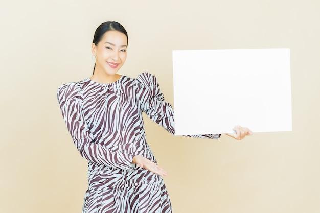 Portret pięknej młodej azjatyckiej kobiety z pustym białym billboardem na beżu