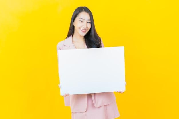 Portret pięknej młodej azjatyckiej kobiety z pustym białym billboardem na żółtej ścianie