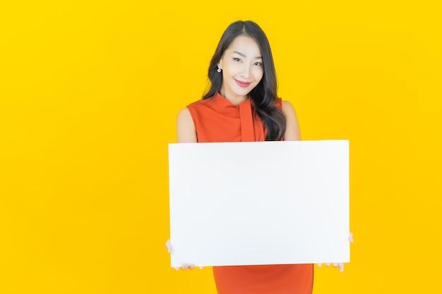 Portret pięknej młodej azjatyckiej kobiety z pustym białym billboardem na żółto