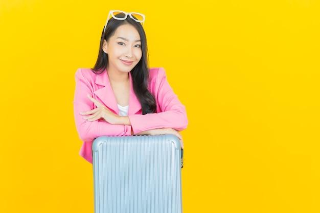 Portret pięknej młodej azjatyckiej kobiety z torbą bagażową i paszportem gotowym do podróży