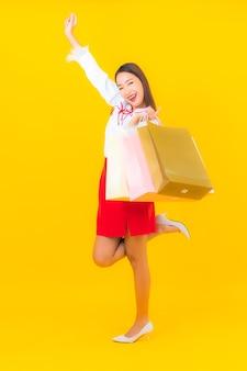 Portret pięknej młodej azjatyckiej kobiety z torbą na zakupy i kartą kredytową na żółto
