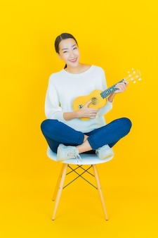 Portret pięknej młodej azjatyckiej kobiety z ukulele na żółto