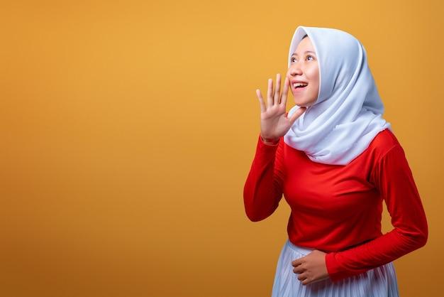 Portret pięknej młodej azjatyckiej kobiety z wyrazem krzyku na żółtym tle