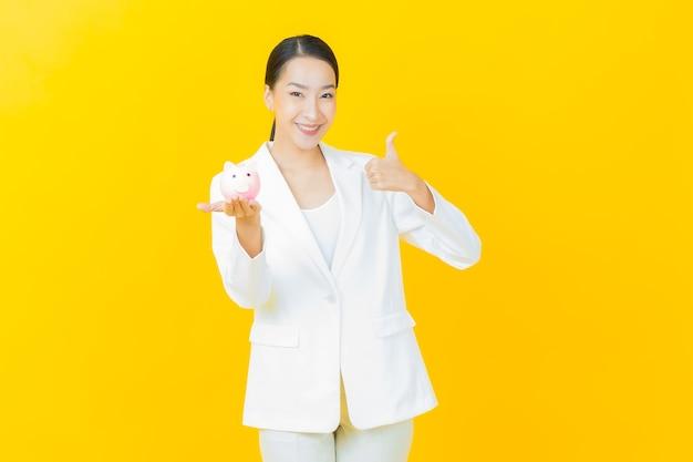 Portret pięknej młodej azjatyckiej kobiety ze skarbonką na kolorowej ścianie