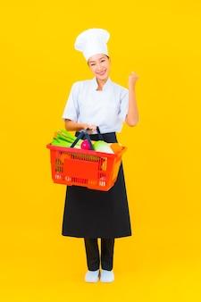 Portret pięknej młodej azjatyckiej kucharki z koszem spożywczym z supermarketu na żółtym tle na białym tle