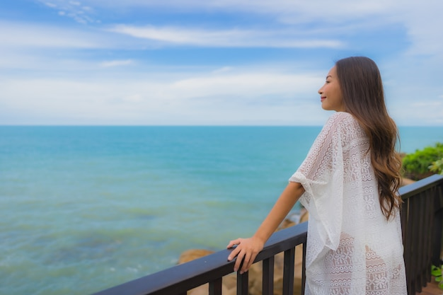 Portret pięknej młodej azjatykciej kobiety morza plaży przyglądający ocean dla relaksuje w wakacje wakacje podróży