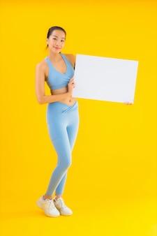 Portret pięknej młodej azjatykciej kobiety odzieży sportwear przedstawienia pusty biały billboard na kolorze żółtym