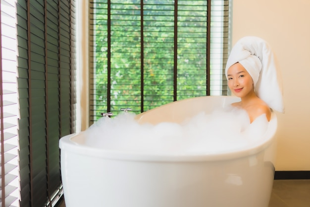 Portret pięknej młodej azjatykciej kobiety szczęśliwy uśmiech relaksuje bierze skąpanie w wannie