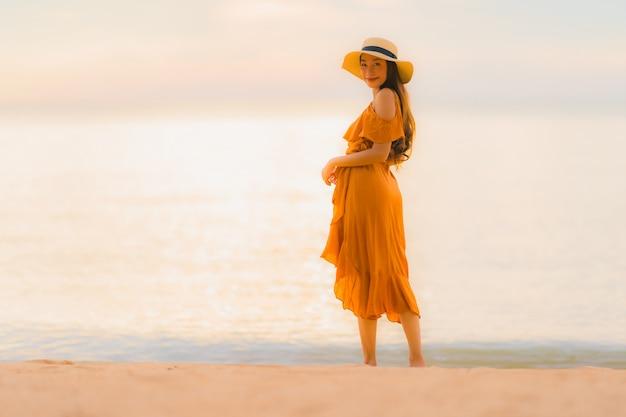 Portret pięknej młodej azjatykciej kobiety szczęśliwy uśmiech relaksuje na plażowym dennym oceanie
