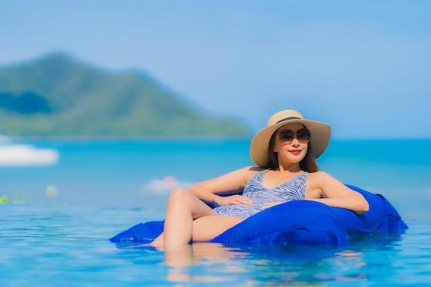 Portret pięknej młodej azjatykciej kobiety szczęśliwy uśmiech relaksuje w pływackim basenie przy hotelowego kurortu oceanu neary denną plażą na niebieskim niebie