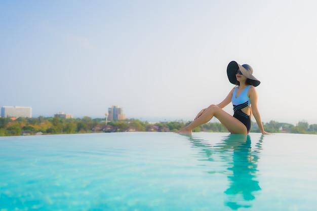 Portret pięknej młodej azjatykciej kobiety szczęśliwy uśmiech relaksuje wokoło plenerowego pływackiego basenu w hotelowym kurorcie