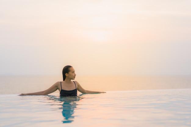 Portret pięknej młodej azjatykciej kobiety szczęśliwy uśmiech relaksuje wokoło pływackiego basenu w hotelowym kurorcie