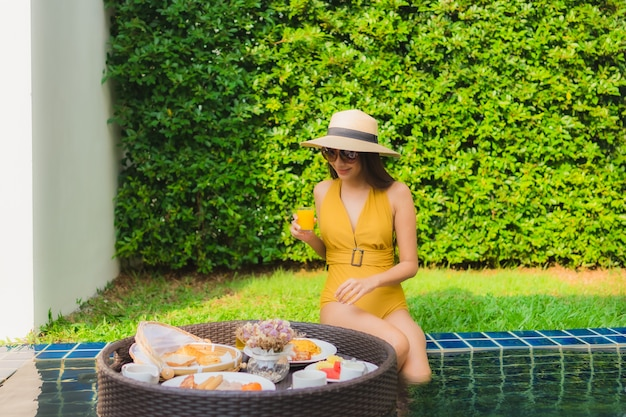 Portret pięknej młodej azjatykciej kobiety szczęśliwy uśmiech relaksuje z śniadaniem unosi się wokoło pływackiego basenu