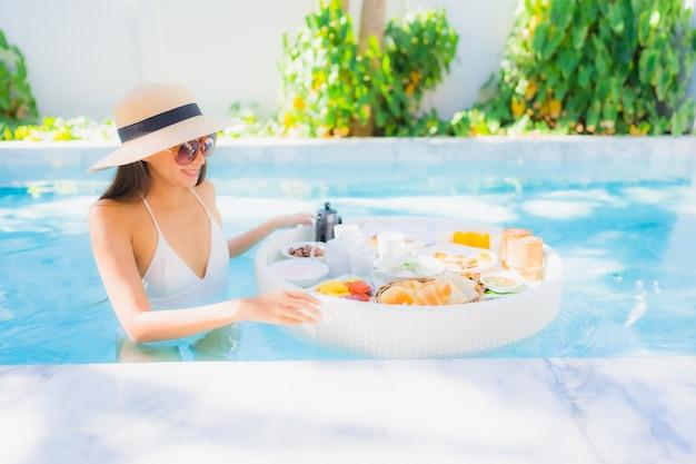 Portret pięknej młodej azjatykciej kobiety szczęśliwy uśmiech z spławowym śniadaniem w tacy na pływackim basenie
