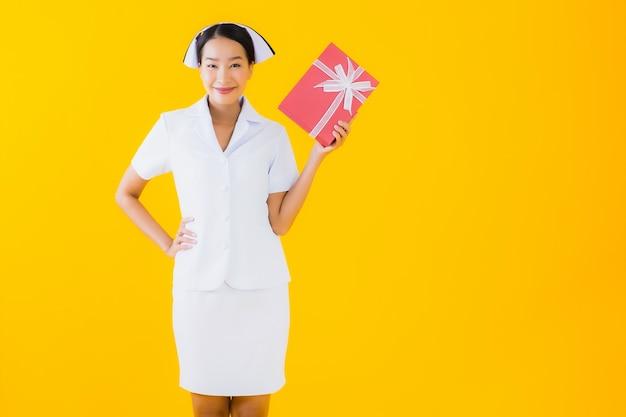 Portret pięknej młodej azjatykciej kobiety tajlandzka pielęgniarka z czerwonym prezenta pudełkiem
