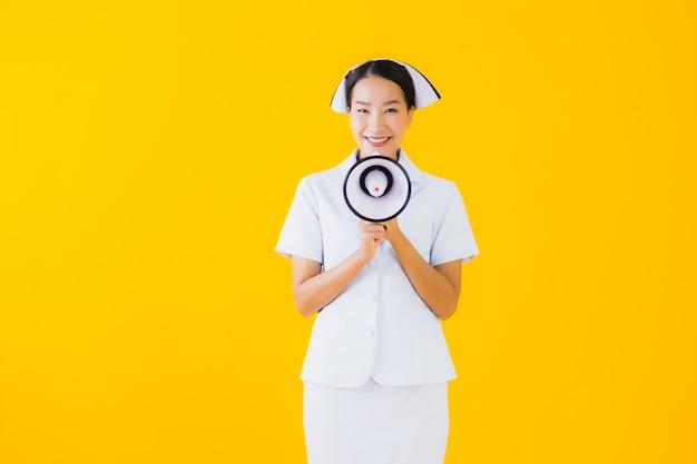Portret pięknej młodej azjatykciej kobiety tajlandzka pielęgniarka z megafonem dla komunikuje
