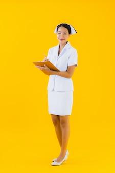 Portret pięknej młodej azjatykciej kobiety tajlandzka pielęgniarka z pustą białą deską