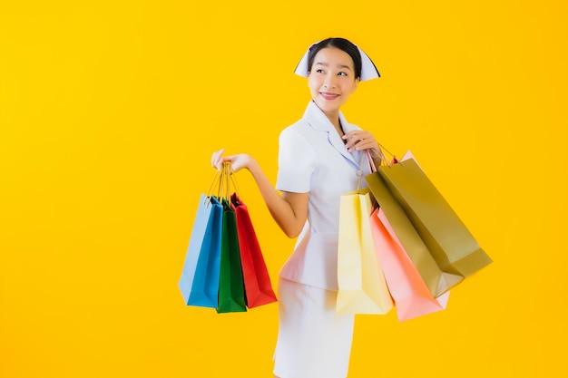 Portret pięknej młodej azjatykciej kobiety tajlandzka pielęgniarka z torba na zakupy i kredytową kartą