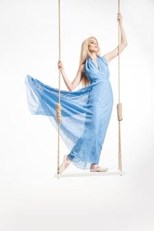 Portret pięknej młodej baletnicy stojącej na huśtawkach w niebieskiej sukience i pointes.isolated.