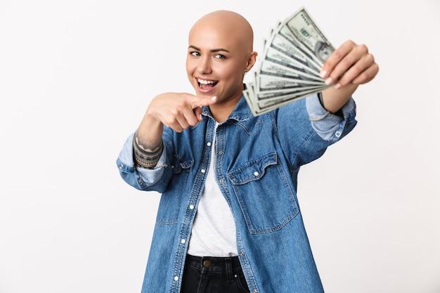 Portret pięknej młodej, bezwłosej kobiety noszącej zwykłe ubrania stojącej na białym tle, pokazującej banknoty pieniędzy
