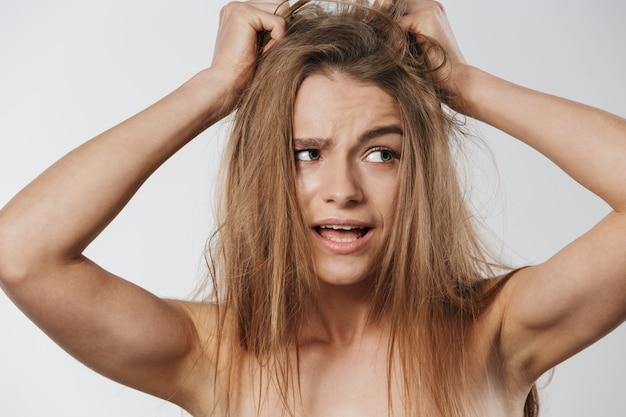 Portret pięknej młodej blond półnagiej kobiety dotykającej jej rozczochranych włosów na białym tle