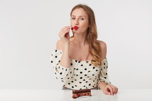 Portret pięknej młodej blondynki o niebieskich oczach z czerwonymi ustami w sukience w kropki. siedzenie przy stole ma zamiar zjeść wiśnię z ciasta. pojedynczo na białym tle.