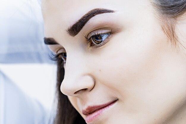 Portret pięknej młodej brunetki o idealnym kształcie brwi na jasnym tle