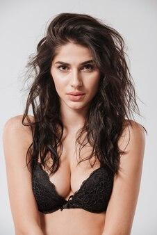 Portret pięknej młodej brunetki w czarnym biustonoszu i patrzącej na przód na białym tle