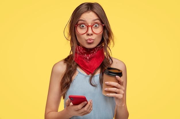 Portret pięknej młodej brunetki w okularach, pozowanie na żółtej ścianie