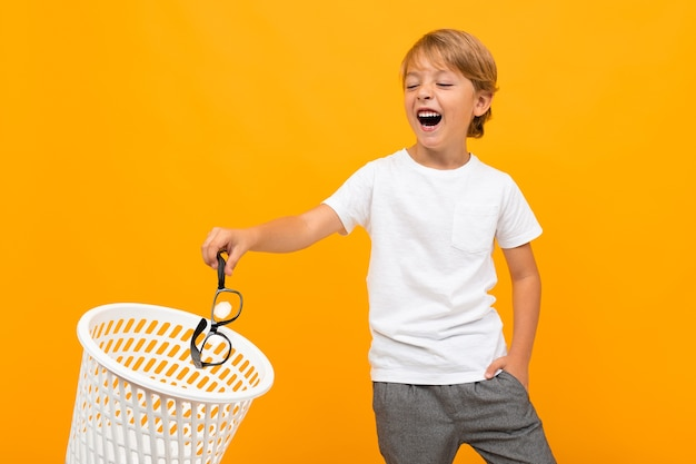 Portret pięknej młodej chłopca rasy kaukaskiej w białej koszulce i szarych spodniach uśmiecha się i wyrzuca okulary