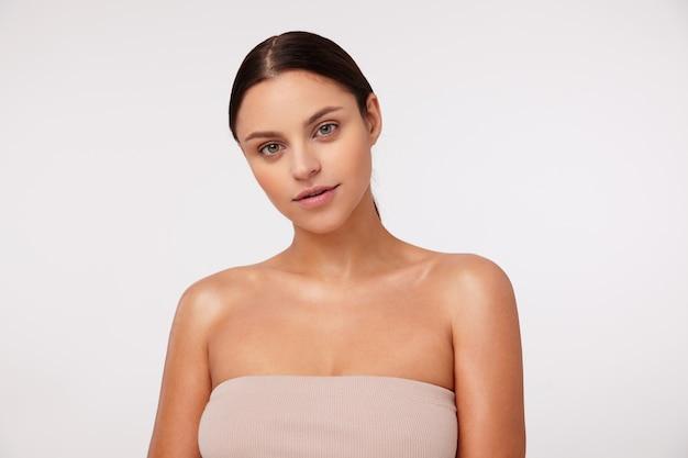 Portret pięknej młodej ciemnowłosej kobiety o swobodnej fryzurze, wyglądającej pozytywnie ze spokojną twarzą, pozującej w beżowym topie z otwartymi ramionami