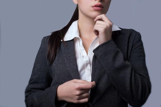 Portret pięknej młodej damy biznesu w garniturze. dziewczyna zwięźle trzyma ręce na twarzy.