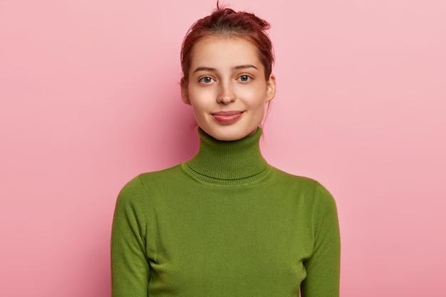 Portret pięknej młodej damy ma ciemne czesane włosy, atrakcyjny wygląd, nosi swobodny zielony golf, chętnie patrzy w kamerę, pozuje na różowym tle
