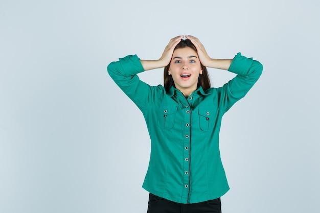 Portret pięknej młodej damy, ściskając głowę rękami w zielonej koszuli i patrząc błogi widok z przodu