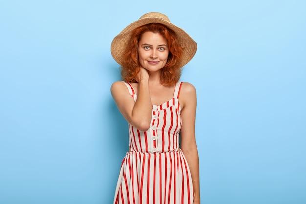 Portret pięknej młodej damy z rudymi włosami, pozowanie w letniej sukience i słomkowym kapeluszu