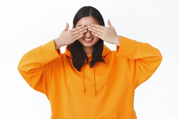 Portret pięknej młodej dziewczyny azjatyckiej w pomarańczowej bluzie z kapturem, zamknij oczy dłońmi i uśmiechając się rozbawiony, świętuje urodziny w oczekiwaniu na prezent niespodziankę, bawi się w chowanego, stoi biała ściana