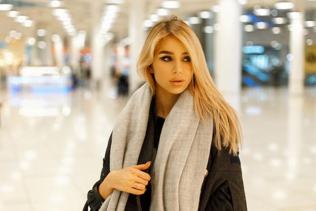 Portret pięknej młodej dziewczyny blondynka w modne ubrania w pomieszczeniu