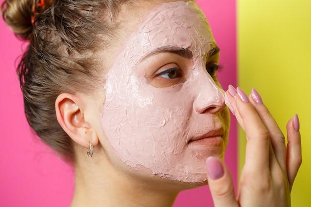 Portret pięknej młodej dziewczyny, która nakłada na twarz odświeżającą maskę, aby odmłodzić i ujędrnić skórę. zabieg upiększający