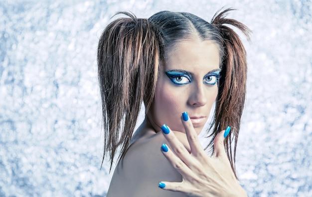 Portret pięknej młodej dziewczyny modelu z warkoczykami, jasnym fantazyjnym makijażem i niebieskim manicure na niewyraźnym metalicznym tle