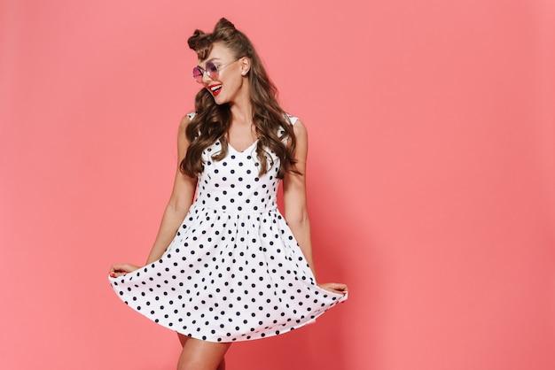 Portret pięknej młodej dziewczyny pin-up na sobie sukienkę i okulary przeciwsłoneczne, stojąc na białym tle, pozowanie