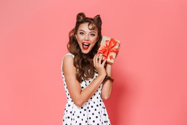 Portret pięknej młodej dziewczyny pin-up na sobie sukienkę stojącą na białym tle, pokazując pudełko