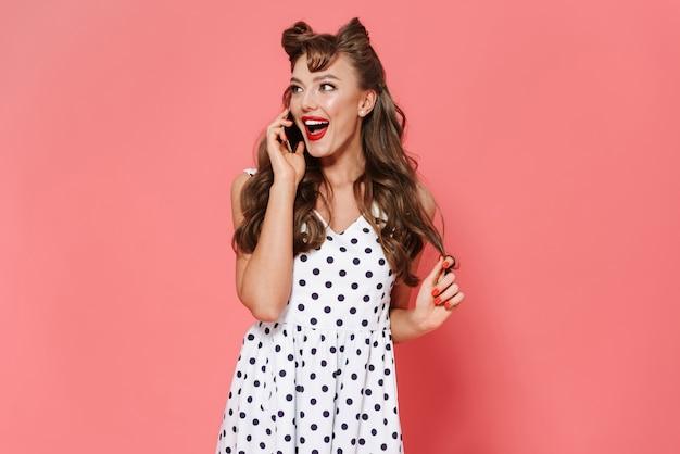 Portret pięknej młodej dziewczyny pin-up na sobie sukienkę stojącą na białym tle, przy użyciu telefonu komórkowego