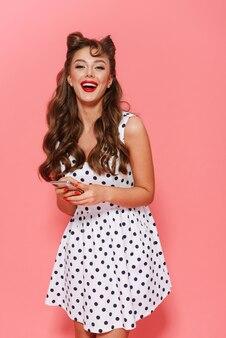 Portret pięknej młodej dziewczyny pin-up na sobie sukienkę stojącą na białym tle, trzymając telefon komórkowy