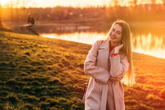 Portret pięknej młodej dziewczyny przed jeziorem i zachodem słońca. ciepłe kolory zachodu słońca.