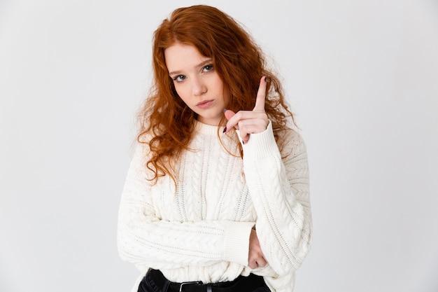 Portret pięknej młodej dziewczyny redheaded stojącej na białym tle nad białym tle, skierowaną w górę