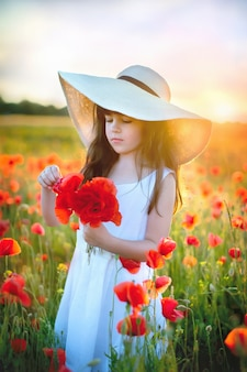 Portret pięknej młodej dziewczyny romantyczny z kwiatami maku w ręku pozowanie na tle pola. noszenie słomkowego kapelusza.