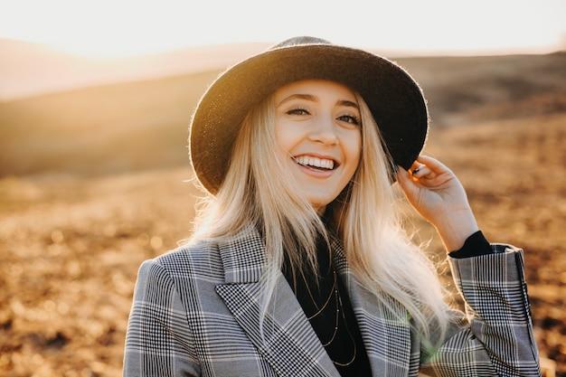 Portret pięknej młodej dziewczyny, śmiejąc się i patrząc na kamery z ręką na kapeluszu przed wschodem słońca podczas odkrywania nowych miejsc w czasie wakacji.