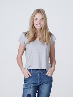 Portret pięknej młodej dziewczyny uśmiechnięte. kobieca twarz z zębatym uśmiechem. atrakcyjna blond dziewczyna pozuje w studio w dorywczo t shirt
